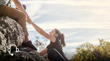 Mann hilft Frau den Felsen hochzuklettern
