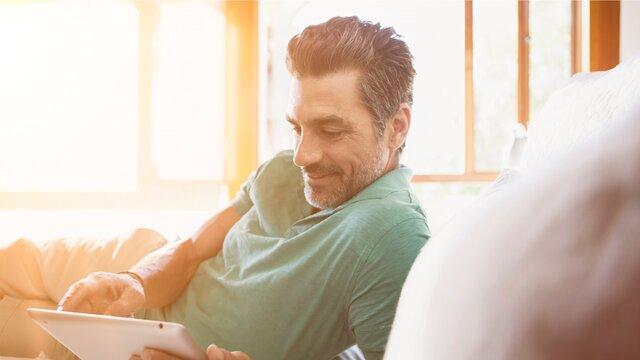 Erwachsener Mann blickt lächelnd auf sein Tablet