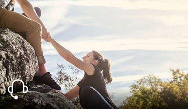 Mann hilft Frau beim hochsteigen auf einen Felsen