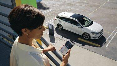 My Renault App Vorteile Frau mit Handy und PlugIn Hybrid