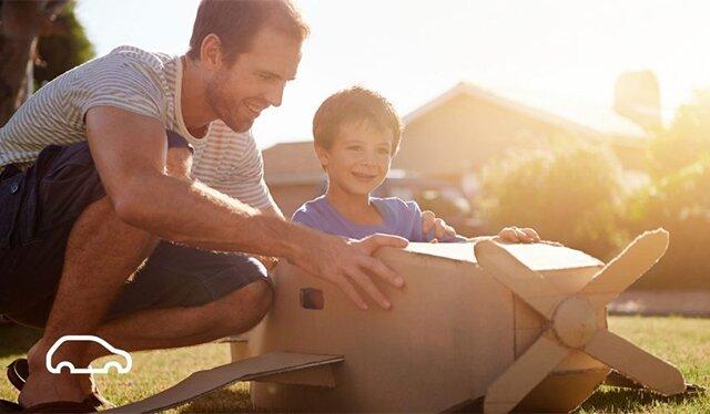 Vater baut einen Pappflieger mit seinem jungen Sohn im Garten