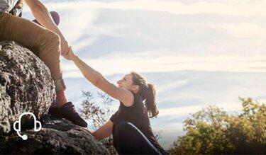 Mann hilft Frau beim Hochklettern auf einen Felsen