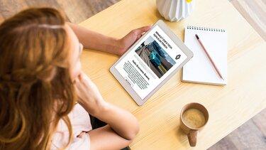 Frau betrachtet den Renault Electric Newsletter auf dem Tablet