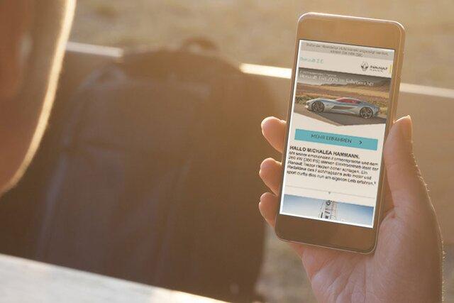 Frau betrachtet den Renault Newsletter auf dem Handy
