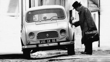 Mann öffnet die Tür eines Renault R4 (Schwarz Weiß Aufnahme)