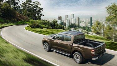 Renault Alaskan auf Landstraße mit Blick auf Skyline