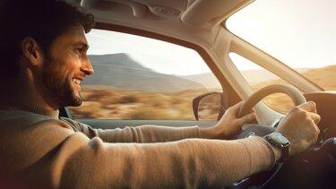 Mann fährt mit Renault durch die Landschaft