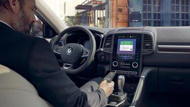 Geschäftsmann verbindet sein Smartphone mit dem R-Link 2 im Renault Koleos