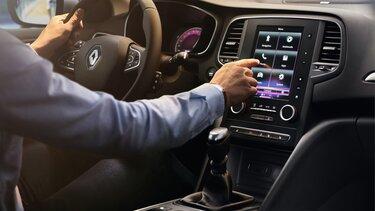 Mann bedient das R-LINK 2 Multimediasystem im Renault Mégane Grandtour