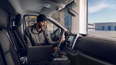 Handwerker arbeitet im mobilen Büro im Renault Trafic