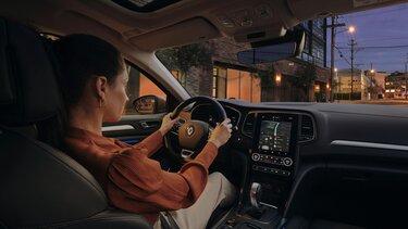 Frau fährt im Renault Megane Grandtour am Abend durch die Stadt