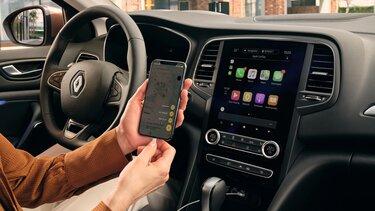 Frau lädt iPhone im Renault Mégane Grandtour
