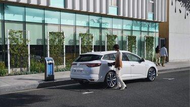 Frau tankt den Renault MEGANE Grandtour Plug-in Hybrid an der Ladestation
