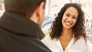 Frau unterhält sich mit Mann und lächelt
