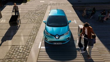 Vater und Kind stehen an der Ladestation eines neuen Renault ZOE