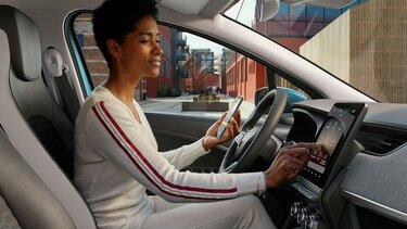 Frau steuert Display ihres Renault ZOE E-Tech