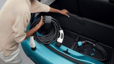 Frau verstaut Ladekabel in den doppelten Kofferraumboden vom ZOE