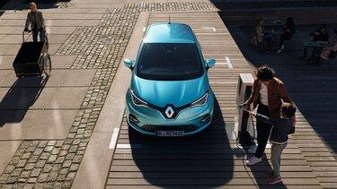 Vater und Kind stehen an der Ladestation eines Renault ZOE E-Tech