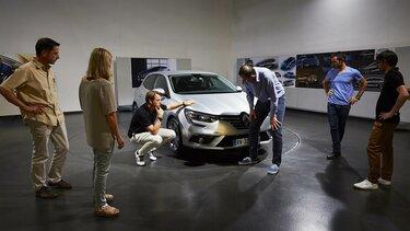 Menschen versammelt um einen weißen Renault