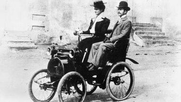Der junge Louis Renault fährt einen mit einem Renault Prototyp durch die Straßen von Paris 1898