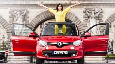 Frau mit gelbem Anzug steht in einem roten Renault mit offenem Schiebedach