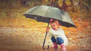 Mädchen hält Regenschirm im Regen auf