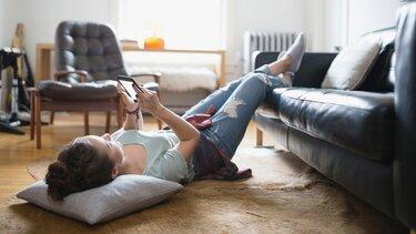 Offre atelier - jeune femme allongée sur un tapis avec son smartphone