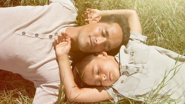 Vater und Tocher lieger unbekümmert in der Sonne