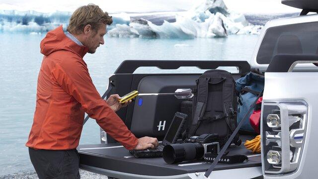 Mann mit seiner Fotoausrüstung und seinem Gepäck auf der Heckfläche eines Renault ALASKAN Concept Cars