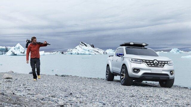 Mann läuft mit seiner Fotoausrüstung an seinem Renault Alaskan Concept Car vorbei
