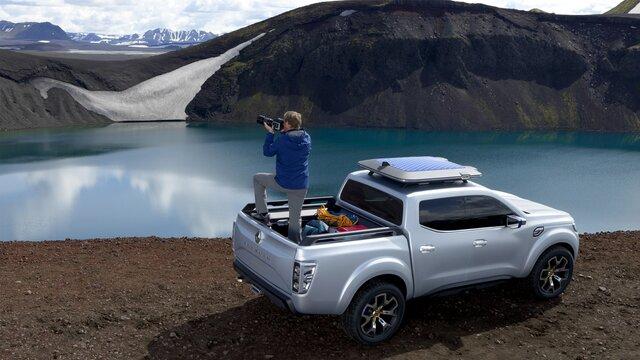 Mann steht auf der Ladefläche eines Renault Alaskan Concept Cars und fotografiert die Seenlandschaft