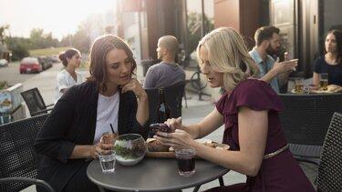 Zwei Frauen schauen sich in einem Cafe etwas auf dem Smartphone an