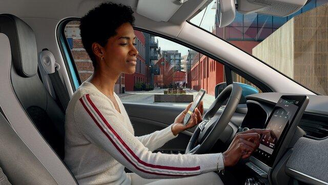 Frau steuert Easy Connect System auf dem Display ihres Renault Fahrzeugs