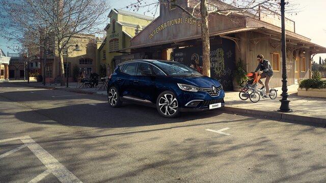 Gelber Renault Scénic und fröhliche Familie