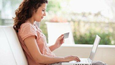kobieta korzysta z laptopa siedząc na sofie w słonecznym pokoju