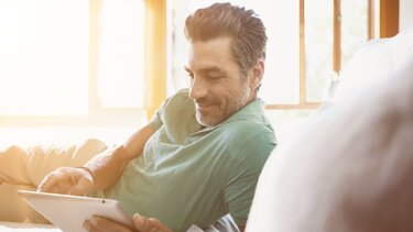 mężczyzna korzysta z tabletu w słonecznym pokoju